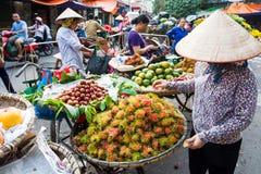 HANOI, VIETNAM - 22 DE MAYO DE 2017: Mujer que vende la fruta tropical en a Foto de archivo