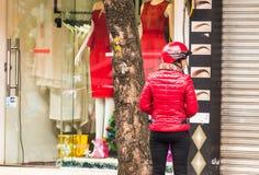 HANOI VIETNAM - DECEMBER 16, 2016: En kvinna i ett rött omslag i bakgrunden av shoppar Kopiera utrymme för text tillbaka sikt Arkivbilder