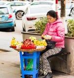 HANOI VIETNAM - DECEMBER 16, 2016: En kvinna säljer frukt på en stadsgata Kopiera utrymme för text Royaltyfri Bild