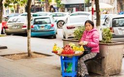HANOI VIETNAM - DECEMBER 16, 2016: En kvinna säljer frukt på en stadsgata Kopiera utrymme för text Arkivbilder