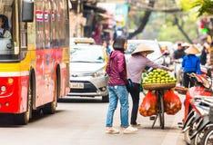 HANOI VIETNAM - DECEMBER 16, 2016: En kvinna säljer frukt på en stadsgata Kopiera utrymme för text Fotografering för Bildbyråer