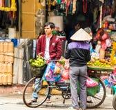 HANOI VIETNAM - DECEMBER 16, 2016: En kvinna säljer grönsaker in Arkivfoto