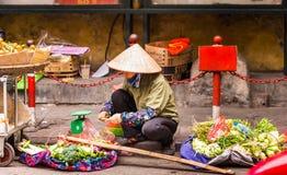 HANOI VIETNAM - DECEMBER 16, 2016: En kvinna säljer grönsaker i den lokala marknaden Royaltyfri Foto