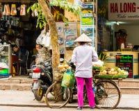 HANOI VIETNAM - DECEMBER 16, 2016: En kvinna säljer grönsaker i den lokala marknaden Kopiera utrymme för text Fotografering för Bildbyråer