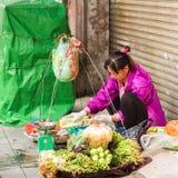 HANOI VIETNAM - DECEMBER 16, 2016: En kvinna säljer grönsaker i den lokala marknaden Närbild Arkivbilder