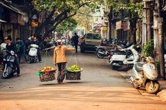 Hanoi Vietnam - 21 December, 2014: Gatuförsäljaren går över gatan Royaltyfria Foton