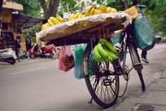 Hanoi Vietnam - 22 December, 2012: Gatuförsäljaretjänstledigheterna banancykeln i gatan Royaltyfria Bilder