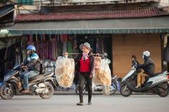 Vietnam, street vendor in Hanoi city. Hanoi, Vietnam-December 17, 2013. Street vendor selling local delicacies carried on a pole across her shoulders and walks Stock Photos