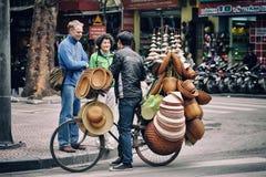 Hanoi Vietnam - 22 December, 2012: Turisterna köper några traditionella souvenir från gatuförsäljaren Arkivfoto