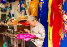 HANOI, VIETNAM - 16 DICEMBRE 2016: La cucitrice cuce i vestiti sul mercato locale fotografie stock
