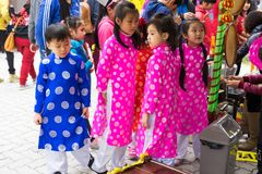 Hanoi, Vietnam - Feb 7, 2015: Children with Vietnamese traditional long dress Ao Dai playing at Vietnamese lunar new year festival. Organized at Vinschool stock images