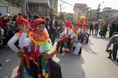 Hanoi, Vietnam - Feb 5, 2017: Men with women dress performing ancient dance called Con Di Danh Bong - Prostitutes beat the drum at. Spring festival in Trieu royalty free stock photo