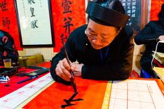 HANOI, VIETNAM, FEB 14, 2018: Old master is writing ancient letter for everyone in lunar new year in Hanoi, Vietnam. This is a stock photos