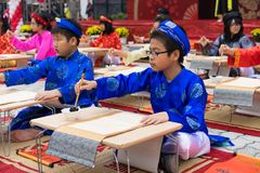 Hanoi, Vietnam - Feb 7, 2015: School children in traditional dress Ao Dai learning with calligraphy at Vietnamese lunar New Year c. Elebrating fair day organized Stock Images