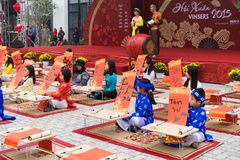 Hanoi, Vietnam - Feb 7, 2015: School children in traditional dress Ao Dai learning with calligraphy at Vietnamese lunar New Year c Royalty Free Stock Photography
