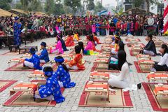 Hanoi, Vietnam - Feb 7, 2015: School children in traditional dress Ao Dai learning with calligraphy at Vietnamese lunar New Year c Royalty Free Stock Photos