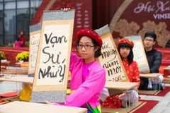 Hanoi, Vietnam - Feb 7, 2015: School children in traditional dress Ao Dai learning with calligraphy at Vietnamese lunar New Year c Stock Image