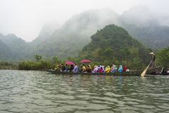 Hanoi, Vietnam - Feb 23, 2014: Tourists on rowing boat on the way to Huong pagoda in festival season by new year time.  Stock Photography