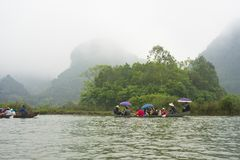 Hanoi, Vietnam - Feb 23, 2014: Tourists on rowing boat on the way to Huong pagoda in festival season by new year time.  Stock Photo