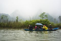 Hanoi, Vietnam - Feb 23, 2014: Tourists on rowing boat on the way to Huong pagoda in festival season by new year time.  Stock Photos