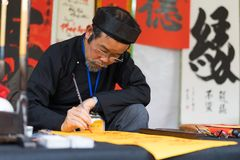 Hanoi, Vietnam - Feb 15, 2015: Vietnamese scholar at lunar new year calligraphy festival organizing at Temple of Literature Van Mi. Eu Stock Photos