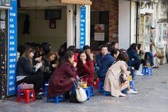 Hanoi, Vietnam - 28 febbraio 2016: La gente beve la frutta del caffè, del tè o del succo sulla stalla del caffè sul marciapiede i Fotografia Stock