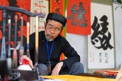 Hanoi, Vietnam - 15 febbraio 2015: Studioso vietnamita al festival lunare di calligrafia del nuovo anno che organizza al tempio d Fotografia Stock