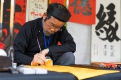 Hanoi, Vietnam - 15 febbraio 2015: Studioso vietnamita al festival lunare di calligrafia del nuovo anno che organizza al tempio d Fotografie Stock