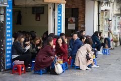 Hanoi, Vietnam - 28 Februari, 2016: De mensen drinken koffie, thee of sapfruit op koffiebox op stoep in de straat van Nha Tho, ce Stock Foto