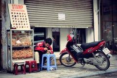 Hanoi Vietnam - 05 Februari, 2012: Mannen gör stämplarna för kunder i trottoaren Royaltyfri Bild