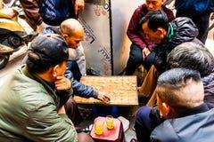 Hanoi Vietnam - Februari 13 2018: Två män som spelar den strategiska brädeleken för två kallade spelare, går i gatorna av Hanoi arkivfoto
