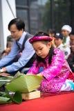 Hanoi, Vietnam - 14 gennaio 2017: Vestito tradizionale Ao DAI da usura della bambina che impara incitare Chung ad agglutinare a m Fotografia Stock
