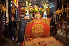 Hanoi, Vietnam - 22 giugno 2017: Uomo anziano che prepara le offerti di culto sull'altare in vacanza in casa comunale così al vil Fotografia Stock Libera da Diritti