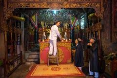 Hanoi, Vietnam - 22 giugno 2017: Uomo anziano che prepara le offerti di culto sull'altare in vacanza in casa comunale così al vil Immagine Stock Libera da Diritti