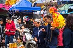 Hanoi, Vietnam - 26. Januar 2017: Eine Mutter und ihr Sohn nehmen eine kaufende Dekoration und eine Blume des Wegs für vietnamesi Stockfotos