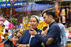 Hanoi, Vietnam - 26. Januar 2017: Eine Mutter und ihr Sohn nehmen eine kaufende Dekoration und eine Blume des Wegs für vietnamesi Stockbilder