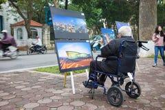 Hanoi, Vietnam - 22 Januari, 2016: De oude mensenzitting op rolstoel let op foto bij openluchtfototentoonstelling naast het meer  Royalty-vrije Stock Foto's