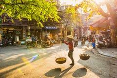 Hanoi Vietnam - 13 Januari, 2015: En försäljare går in i den gamla gatan Arkivbilder
