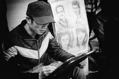 Hanoi Vietnam - Januari 17, 2012: Målareattraktionen ståendemålningen för kunder i trottoaren Royaltyfri Fotografi