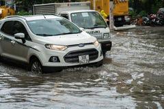 Hanoi, Vietnam - 17. Juli 2017: Auto spritzt durch eine große Pfütze auf überschwemmter Straße nach starkem Regen in Minh Khai, H Lizenzfreie Stockfotografie