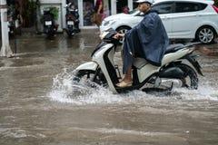 Hanoi, Vietnam - 17. Juli 2017: Ein Motorradfahrer reitet entlang überschwemmte Minh Khai-Straße in Hanoi-Stadt, Vietnam Lizenzfreie Stockfotos