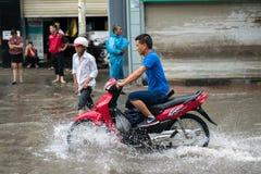 Hanoi, Vietnam - 17. Juli 2017: Ein Motorradfahrer reitet entlang überschwemmte Minh Khai-Straße in Hanoi-Stadt, Vietnam Stockbilder