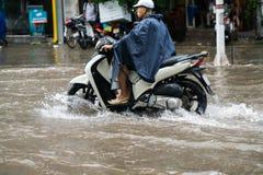 Hanoi, Vietnam - 17. Juli 2017: Ein Motorradfahrer reitet entlang überschwemmte Minh Khai-Straße in Hanoi-Stadt, Vietnam Stockfotografie