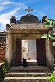 Hanoi, Vietnam - 17. Juli 2016: Gealtertes Kirchentor mit heiligem Kreuz auf Spitze, vietnamesischem konischem Hut und Stock gehe Lizenzfreies Stockfoto