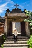 Hanoi, Vietnam - 17. Juli 2016: Gealtertes Kirchentor mit heiligem Kreuz auf Spitze, vietnamesischem konischem Hut und Stock gehe Lizenzfreie Stockfotografie