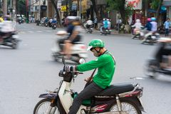 Hanoi Vietnam - Juli 7, 2017: Grip den väntande på kunden för mopedchauffören på den lodisTrieu gatan Skrivna in Vietnam i 2014,  arkivfoto