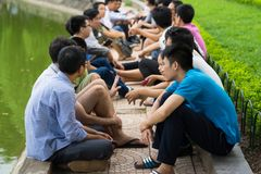 Hanoi, Vietnam - July 3, 2016: Group of students learn to speak English with English native foreigners at Hoan Kiem lake. A lot of. Students choose this way to Royalty Free Stock Photography