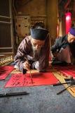 Hanoi, Vietnam - Jun 22, 2017: De geleerde schrijft zo Chinese kalligrafiekarakters in communaal huis bij dorp, het district van  Stock Foto