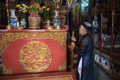 Hanoi, Vietnam - Jun 22, 2017: Oude mens die vereringsdienstenaanbod op altaar op vakantie in communaal huis voorbereiden bij zo  Stock Foto