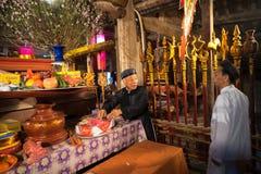 Hanoi, Vietnam - Jun 22, 2017: Oude mens die vereringsdienstenaanbod op altaar op vakantie in communaal huis voorbereiden bij zo  Stock Fotografie
